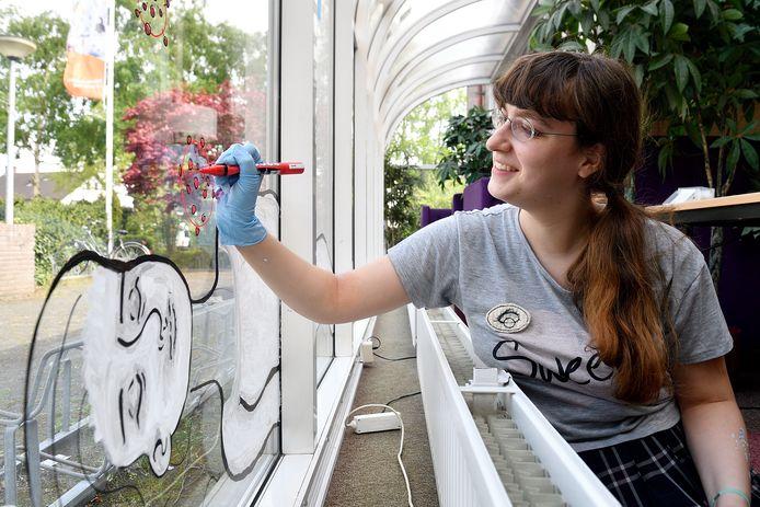 Lotte Wolf werkt aan een kunstwerk op de ramen van de Nijkerkse bibliotheek.