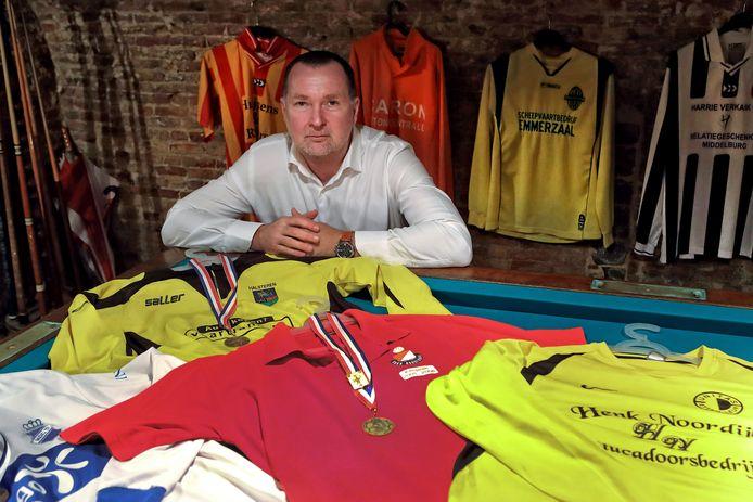 Kees de Rooij tussen de shirts van de clubs waar hij of als voetballer of als trainer geweest is.