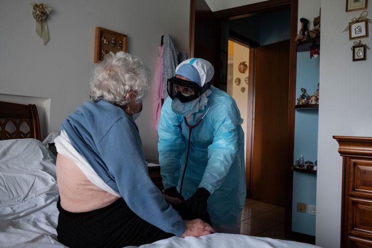 Een mevrouw met griepklachten wordt thuis onderzocht door dokter Villa. Beeld Giulio Piscitelli