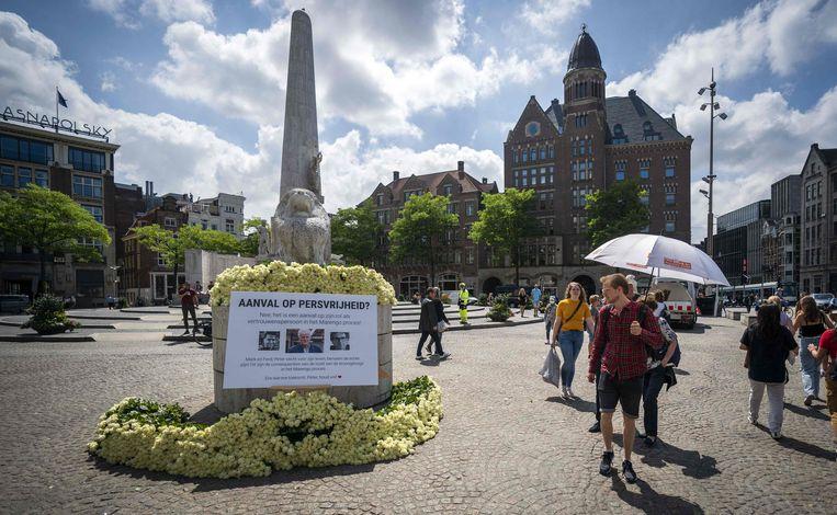 Witte rozen voor journalist Peter R. de Vries liggen bij het Nationaal Monument op de Dam, Amsterdam. Beeld AFP