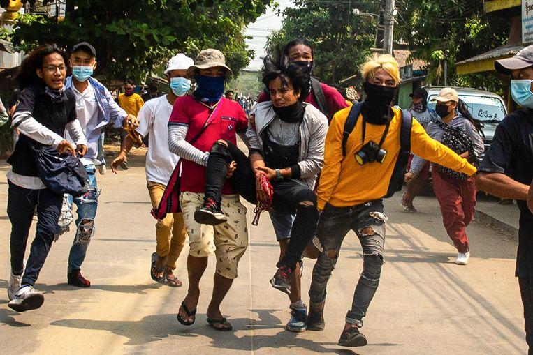 Demonstranten dragen een andere gewonde betoger. Beeld AFP
