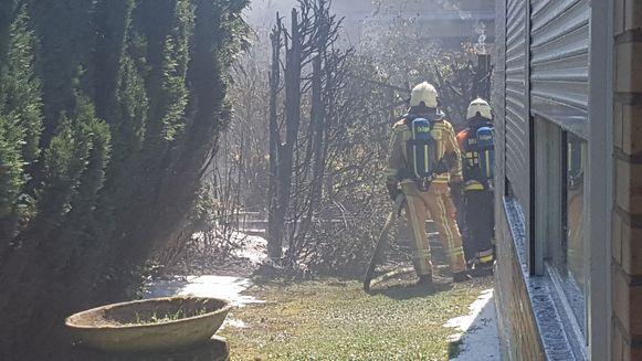 De brandweer tijdens het blussen van de haag en omheining.