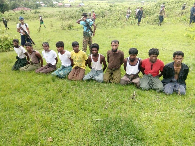 Tien Rohingya-mannen moeten met hun handen achter hun rug vastgebonden knielen voor Myanmarese veiligheidskrachten in het dorpje Inn Din in de staat Rakhine. Archiefbeeld uit 2017.
