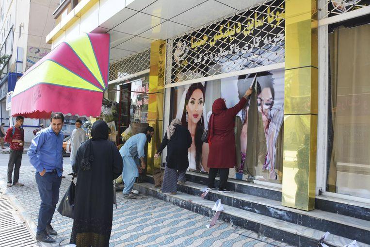 Medewerkers van een schoonheidssalon in Kaboel verwijderen afbeeldingen van vrouwen van de gevel. Beeld BELGAIMAGE