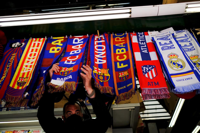 Een verkoper op de Ramblas in Barcelona herschikt sjaaltjes van clubs die een nieuwe, eigen Super League willen, waaronder andere FC Barcelona, Real Madrid en Atlético Madrid.  Beeld Reuters