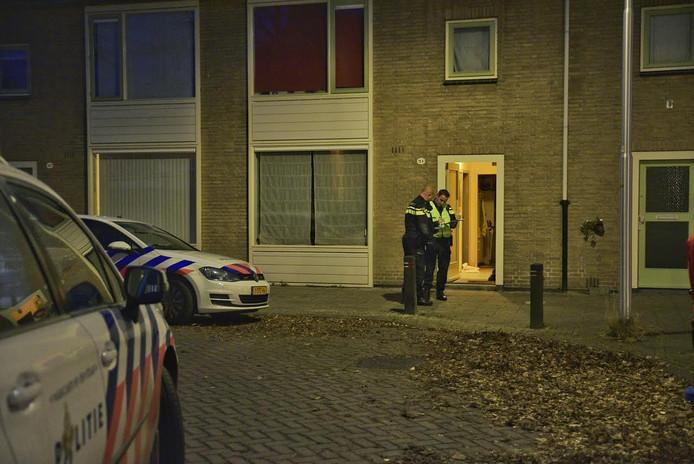 Politieagenten onderzoeken de omgeving van de overvallen woning.