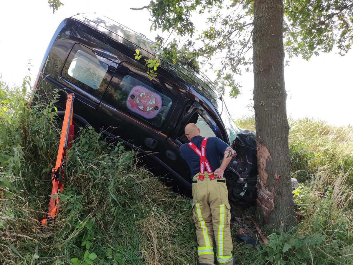 De bestelwagen kwam tegen een boom terecht langs de weg.