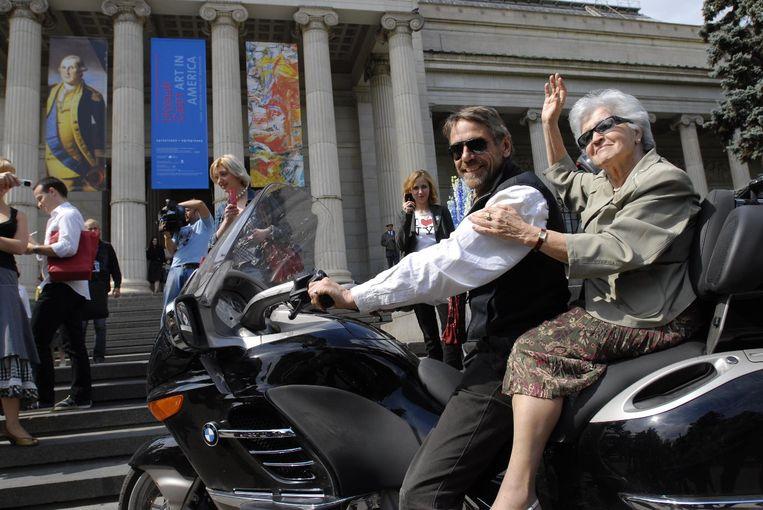 Irina Antonova bij de Engelse acteur Jeremy Irons op de motor.  Beeld The Pushkin Museum
