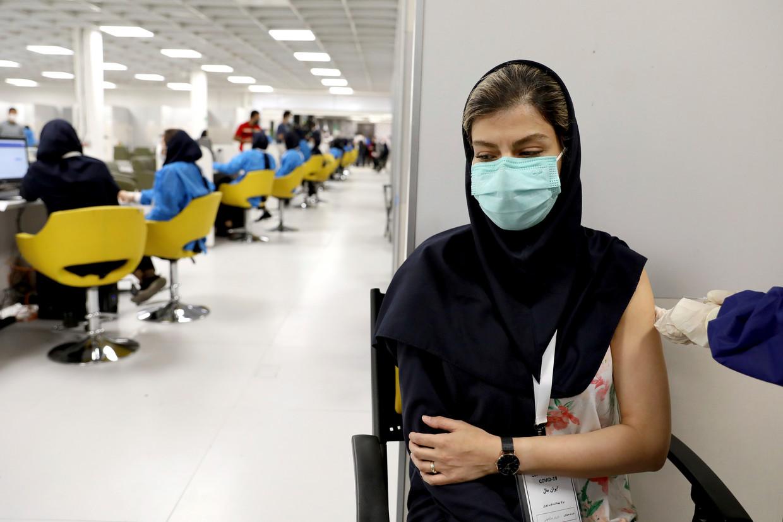 Een Iraanse zorgmedewerker ontvangt half mei in een winkelcentrum in Teheran het coronavaccin van de Chinese farmaceut Sinopharm. Het Europees Geneesmiddelenbureau EMA buigt zich over de toelating van een ander Chinees vaccin, van Sinovac. Beeld AP