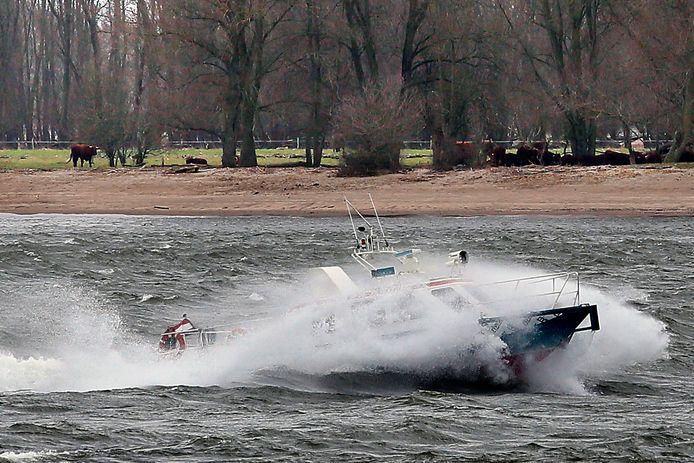 De waterboottaxi baant zich een weg door wind en golven. Er zijn zojuist passagiers afgezet bij Slot Loevestein