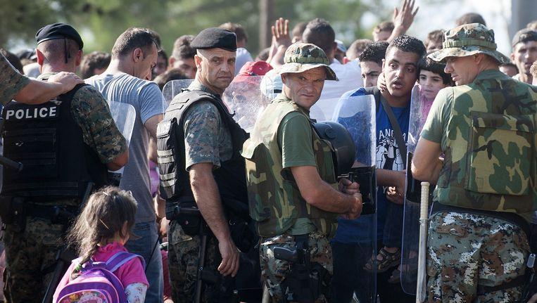 Migranten wachten bij een rij agenten aan de Macedonische grens.
