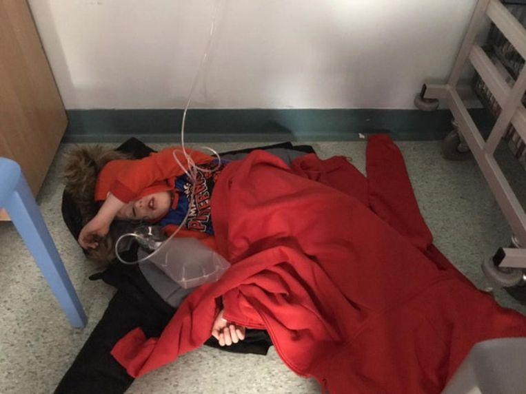 Jack Williment-Barr ligt op de vloer van het ziekenhuis. Zijn moeder fotografeerde het jongetje en deelde de foto met the Yorkshire Evening Post Beeld null