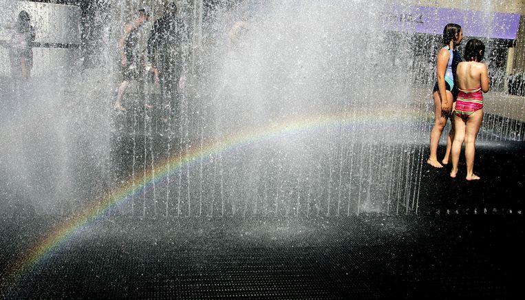 Kinderen spelen in een fontein op de zuidelijke oever van de Thames in Londen. Beeld AP