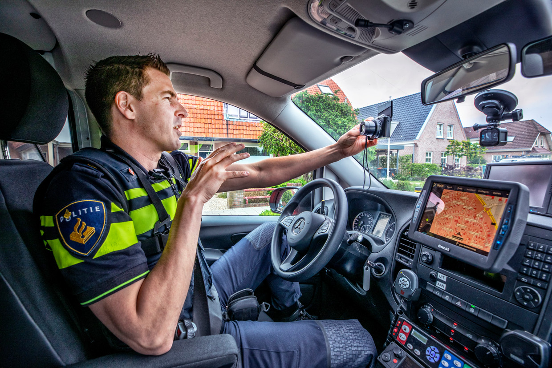 Agent Jan-Willem Schut heeft zijn politieauto geparkeerd om een stukje voor zijn vlog op te nemen. Beeld Raymond Rutting / de Volkskrant