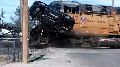 Prius vliegt door de lucht wanneer trein oplegger ramt