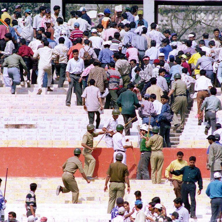 Cricket is soms een beetje oorlog, zeker als het India tegen Pakistan is. Hier jaagt de politie van Calcutta toeschouwers het Eden Garden-stadion uit, nadat er steeds meer waterflessen op het terrein waren gegooid. Toen iedereen buiten was, werd de match hervat. Pakistan won. Beeld AFP