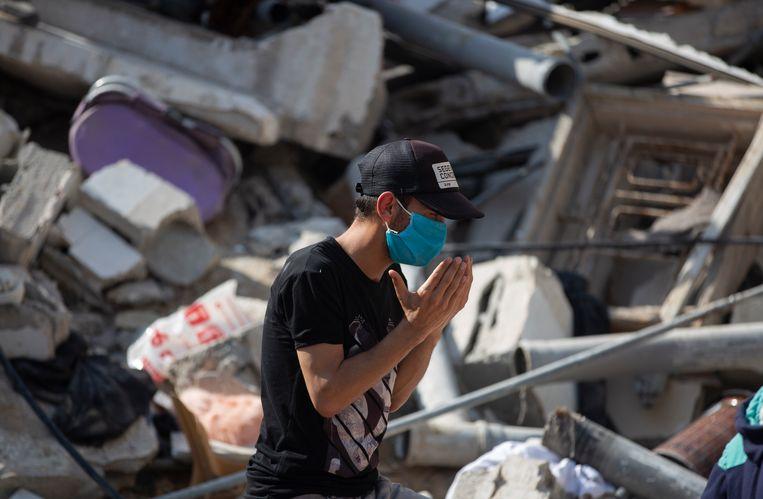 Een Palestijnse man bidt tussen het puin van woningen die door Israëlische raketten zijn verwoest. Beeld AP
