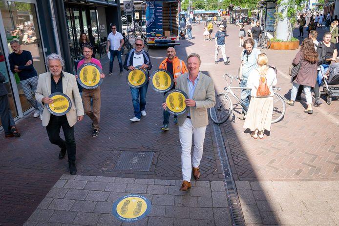 Presentatie van de anti-coronamarkeringen op het plaveisel van de Arnhemse binnenstad vorig jaar. Nieuwe stickers zijn in aantocht. Op de voorgrond: voorzitter Gerard Velthuizen van het Binnenstad Platform Arnhem (links) en wethouder Economische Zaken Jan van Dellen (rechts).