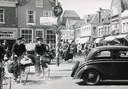 Een drukte van jewelste eind jaren 50 op de Varkensmarkt. Alle verkeer reed van noord naar zuid en van oost naar west, dwars door de binnenstad. Het verkeersbord wijst de weg richting Arnhem (via de Arnhemsestraat), Zwolle (via de Langestraat), Spakenburg (via de Westsingel) en Utrecht (via de Utrechtsestraat).