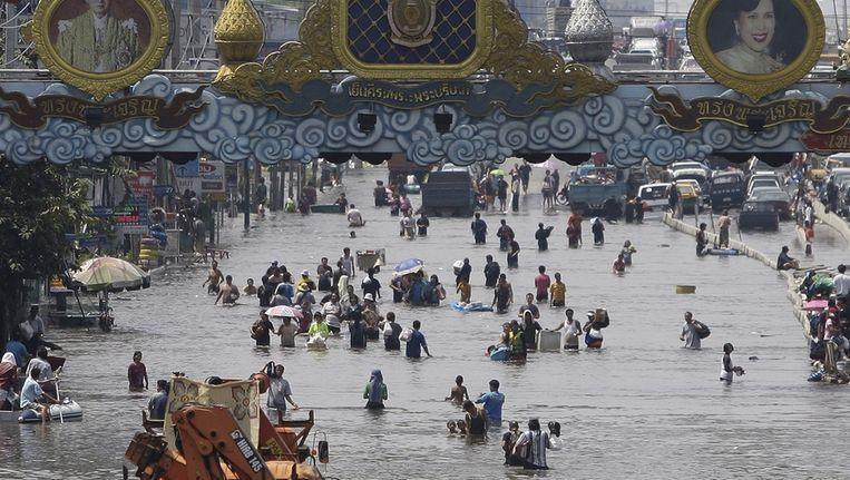 Inwoners van Bangkok waden door de overstroomde straten in de stad. Beeld ap