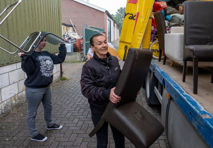 Candida Milia (vooraan) zet een stoel van Kringloopwinkel Ramsjburg in de bijna volle vrachtwagen, die daarna naar Maastricht rijdt.