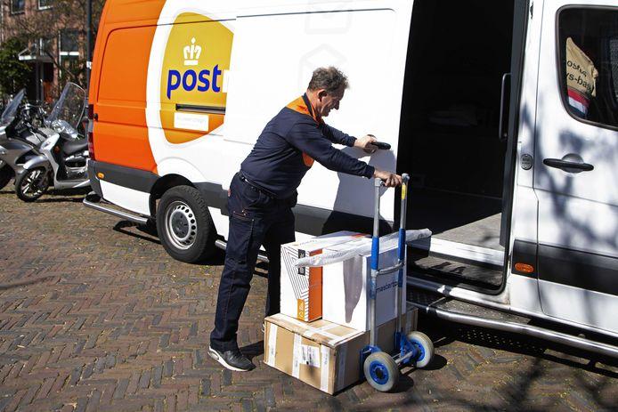 Een postbezorger doet een contactloze bezorging. Bij PostNL is het deze dagen aanzienlijk drukker dan voor de coronacrisis.