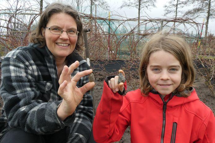 Marleen Simons (l) met haar zoon. Ze vonden een ongeveer 4000 jaar oude pijlpunt in de moestuin in Wijbosch.