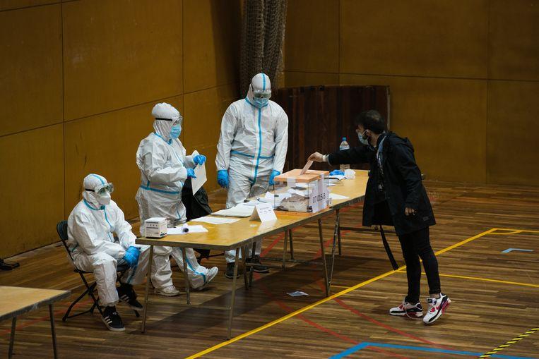 Een man gooit zijn stembiljet in een stembus. Het opkomstpercentage van de Catalaanse verkiezingen was bijzonder laag door het coronavirus. Beeld Getty