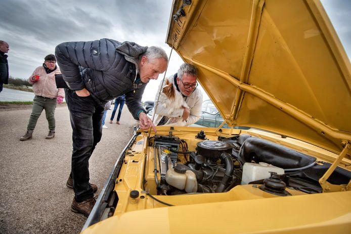 Liefhebbers verdiepen zich in de motortechniek van een klassieker op een oldtimer-evenement in Velp, begin deze maand