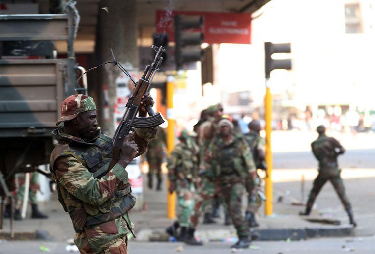 Militairen in de Zimbabwaanse hoofdstad Harare schieten in de lucht om menigten betogers te verspreiden. Er vielen zeker drie doden. Beeld Reuters