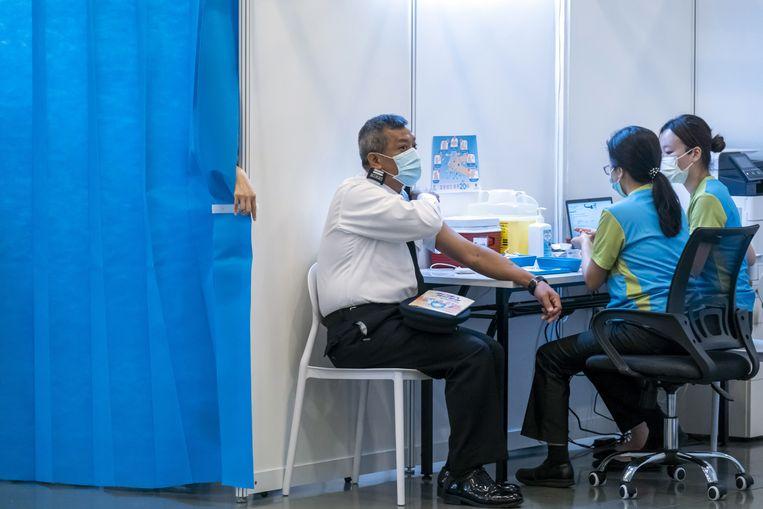 In Hongkong wordt een medewerker van de immigratiedienst ingeënt met het vaccin van Sinovac.  Beeld EPA