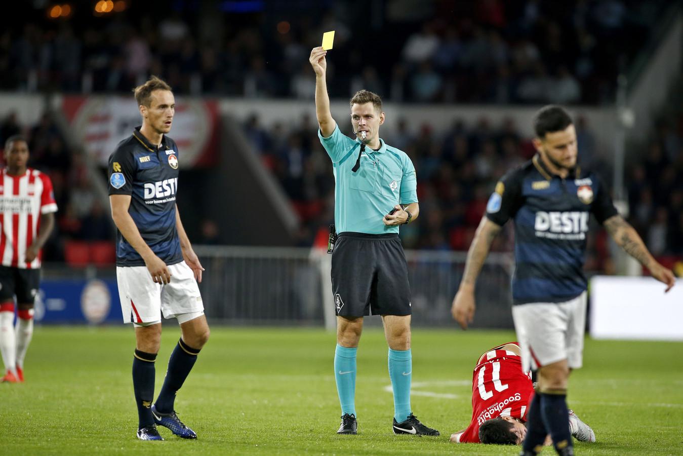 Freek Heerkens (links) krijgt de gele kaart van scheidsrechter Kamphuis.