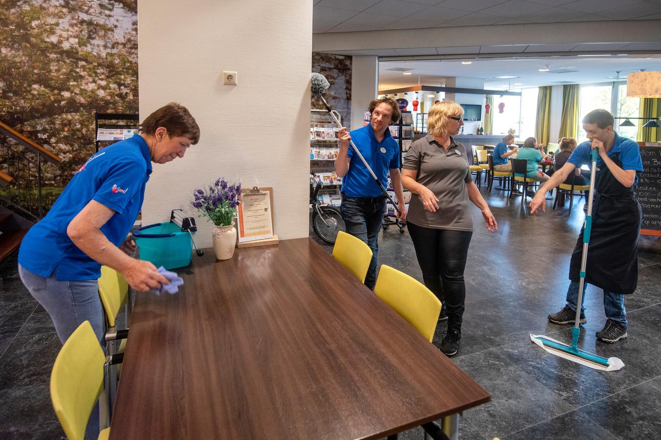 Carolien, Tim en Michael maken, onder leiding van Jolande (bruin shirt), de boel schoon in verpleeg- en verzorgingshuis Sint Jozef.