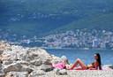 Een dame laaft zich aan de zon op het strand van de Kroatische kustplaats Rijeka, aan de Adriatische Zee.