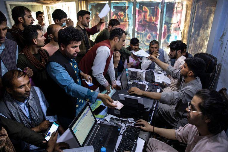 Afghanen die voor de VS hebben gewerkt, proberen in een internetcafé in Kabul een aanvraag rond te krijgen voor een visum. Beeld Getty Images