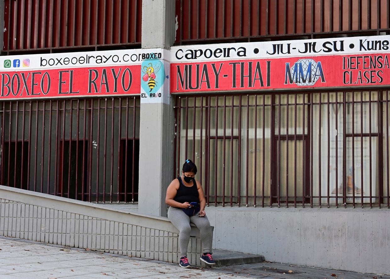Een vrouw checkt haar gsm in Vallecas, Madrid, waar veel gebouwen zijn gesloten vanwege de nieuwe corona-uitbraak. Beeld EPA