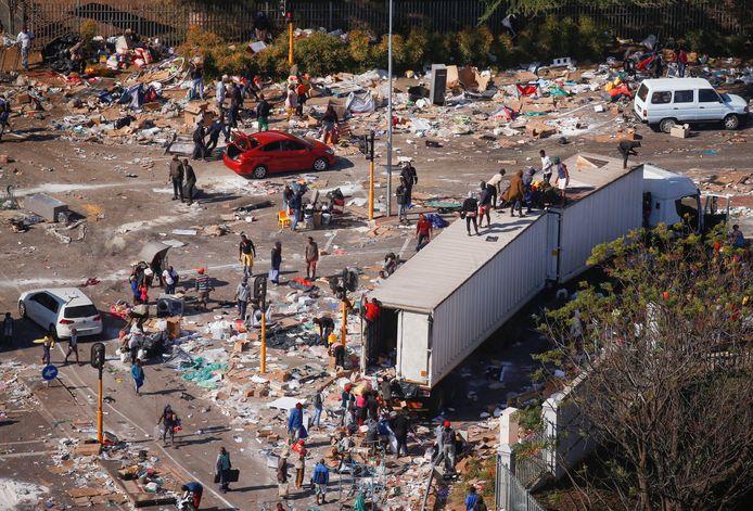 Mensen plunderen een gebied in de buurt van een brandend pakhuis nadat het geweld uitbrak na de gevangenneming van de voormalige Zuid-Afrikaanse president Jacob Zuma, in Durban, Zuid-Afrika