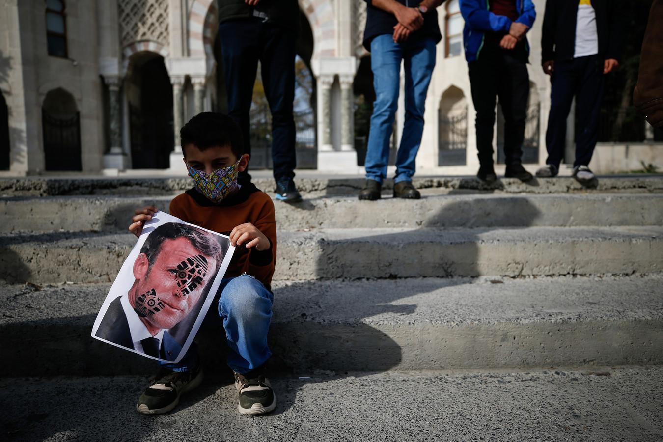 """Onder meer in Bangladesh trokken personen vandaag de straat op om te betogen tegen Frankrijk. De demonstranten hadden plakkaten bij met daarop een karikatuur van Emmanuel Macron en de woorden: ,,Macron is de vijand van vrede""""."""