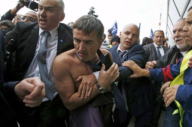 Een directeur van Air France wordt uitgekleed. Zo goed als onvoorstelbaar in veel andere landen. Beeld AFP