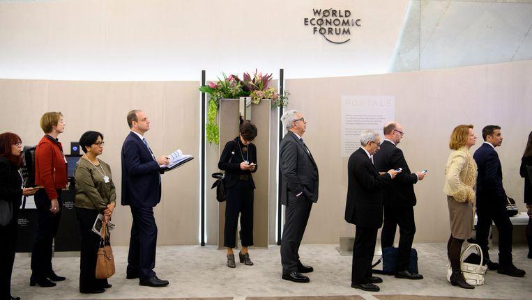 Deelnemers aan het World Economic Forum in Davos staan woensdag in de rij voor een debat. Beeld null