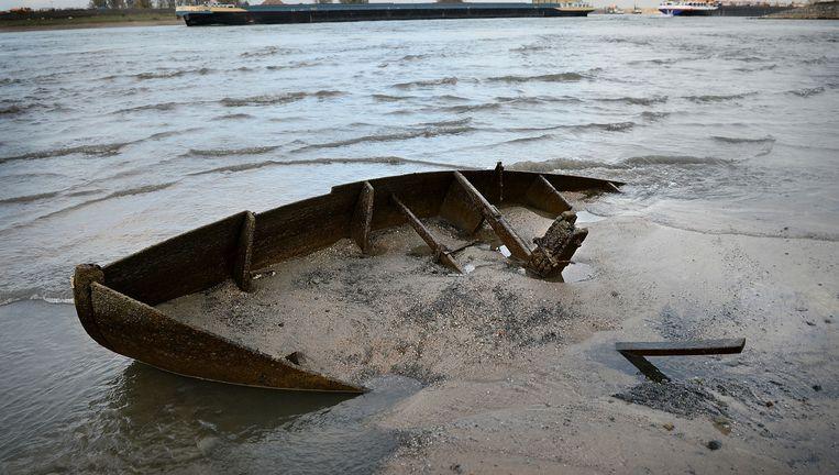 Een ondergelopen bootje in de Waal bij Nijmegen als gevolg van laagwater op de Rijn. Beeld Marcel van den Bergh/Volkskrant