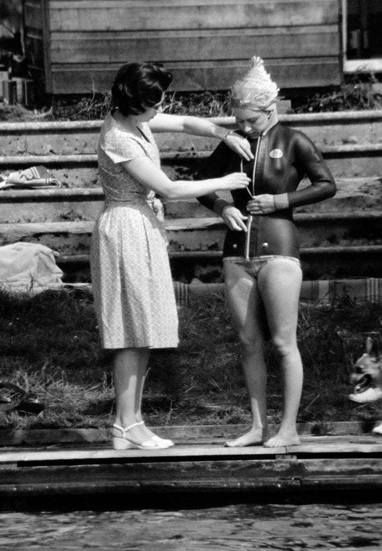 Queen Elizabeth II (l) helpt haar zus prinses Margaret met haar wetsuit om te gaan waterskiën, in juli 1964.  De foto werd gemaakt door Ray Bellisario, de eerste paparazzo die naam waardig. Beeld Popperfoto via Getty Images