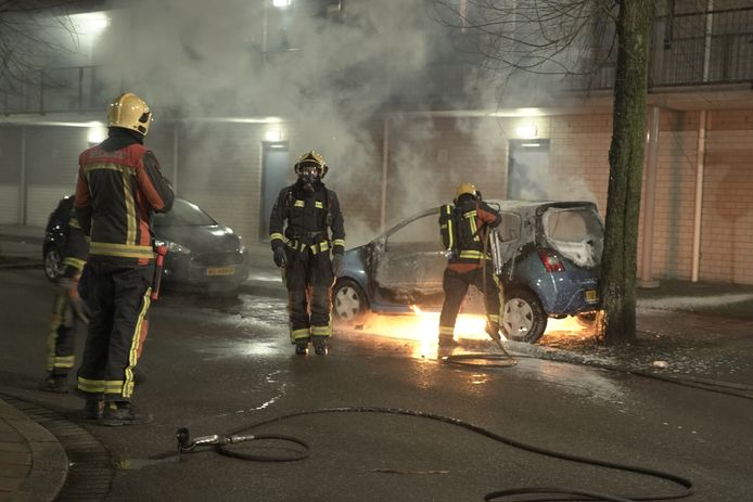 De brandweer blust de auto.