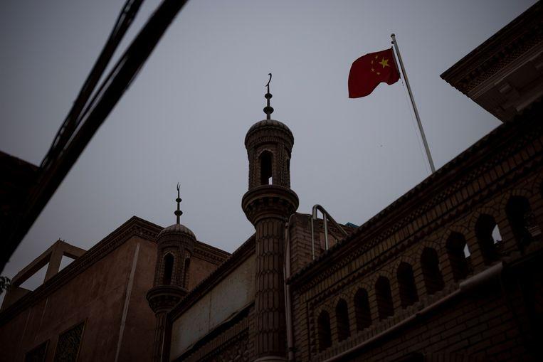 De Chinese vlag bij een moskee in Kashgar, in de Chinese regio  Xinjiang. Beeld REUTERS