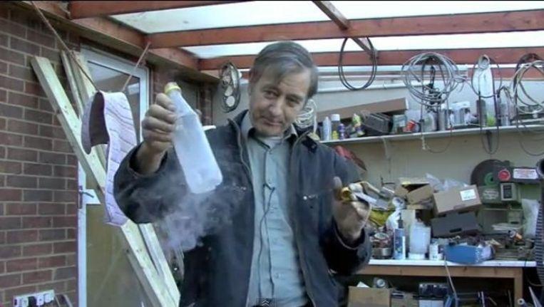 Peter Dearman in zijn garage met een flesje vloeibare lucht waarmee een motortje wordt aangedreven. Beeld