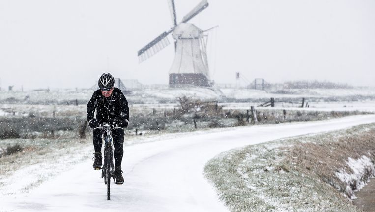 Een fietser in het winterse landschap van de Glimmense polder met op de achtergrond de De Witte Molen uit 1892 aan het Noord-Willemskanaal. Beeld anp