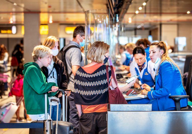 Passagiers tonen de Corona CheckApp op Schiphol. Beeld Raymond Rutting / de Volkskrant