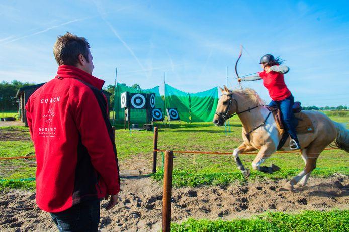 Alles in één blik: Christoph Némethy (links) geeft de amazone tips hoe zij haar paard zodanig moet zien te beheersen dat ze ook nog eens het doel weet te raken.
