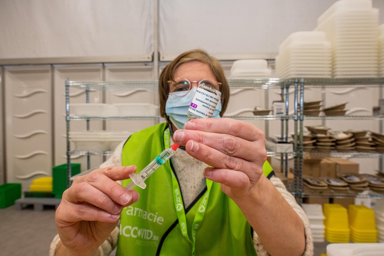 Een verpleegkundige van het vaccinatiecentrum op Spoor-Oost in Borgerhout (Antwerpen) steekt een vaccindosis in een injectiespuit.