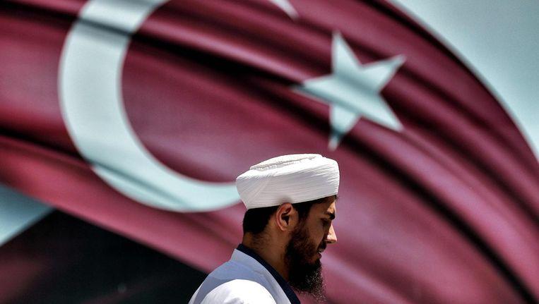 Een imam voor een Turkse vlag tijdens een pro-Erdogan demonstratie in Istanbul. Beeld afp